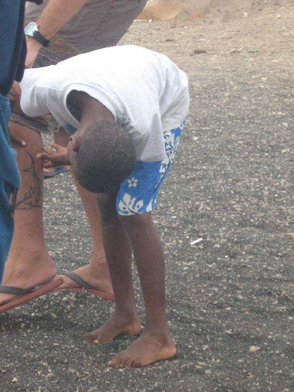 Boy checking out the tattoo of a tourist, Cape Verde
