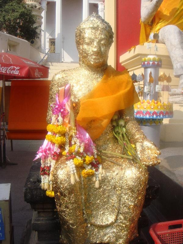 Buddha statue covered in flowers, Nakhon Pathom Thailand