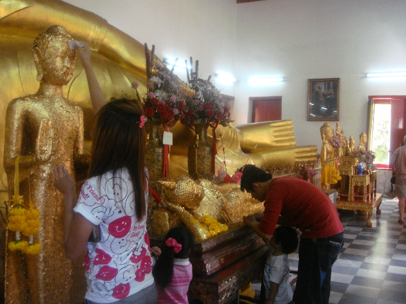Thai family paying respect to the Buddha, Nakhon Pathom Thailand
