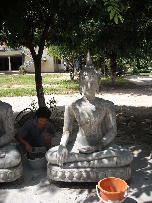 Lao man reconstructing a Buddha, Laos