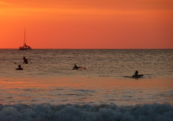 Surfers cathing the waves under a spectacular sunset in Tamarindo, Costa Rica