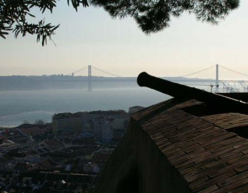 Old canon in Lisbon with a view of the Lisbon Bridge , Portugal